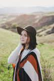Young beautiful woman traveler wearing hat and poncho relaxing on the top of the hill Royalty Free Stock Images