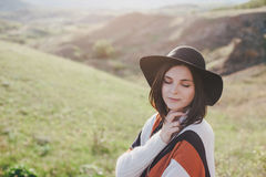 Young beautiful woman traveler wearing hat and poncho relaxing on the top of the hill Stock Images