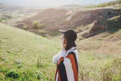 Young beautiful woman traveler wearing hat and poncho relaxing on the top of the hill Stock Photo