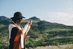 Young beautiful woman traveler wearing hat and poncho taking pictures on her smart phone Royalty Free Stock Image
