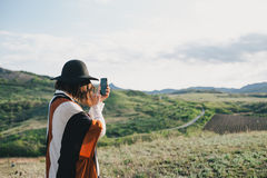 Young beautiful woman traveler wearing hat and poncho taking pictures on her smart phone Stock Photo