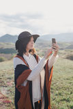 Young beautiful woman traveler wearing hat and poncho taking pictures on her smart phone Stock Image