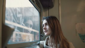 Young beautiful woman traveling by train. Attractive girl looking at window and exploring the landscape outside.