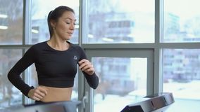 Young beautiful woman on a treadmill in the gym. Fitness concept.  stock footage
