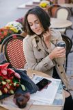 Young beautiful woman in trench coat drinking coffee in a street cafe stock image