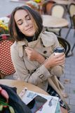 Young beautiful woman in trench coat drinking coffee in a street cafe royalty free stock images