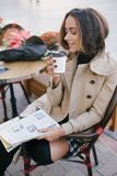Young beautiful woman in trench coat drinking coffee in a street cafe royalty free stock image