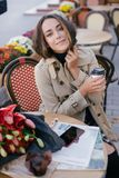 Young beautiful woman in trench coat drinking coffee in a street cafe royalty free stock photography