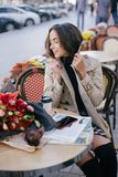 Young beautiful woman in trench coat drinking coffee in a street cafe stock images