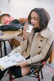 Young beautiful woman in trench coat drinking coffee in a street cafe royalty free stock photo