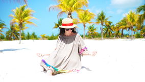 Young beautiful woman on tropical beach with palmtrees stock footage