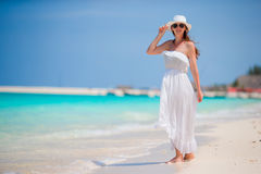 Young beautiful woman during tropical beach vacation. Happy girl in white dress enjoy her summer holidays Stock Photography