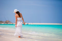 Young beautiful woman during tropical beach vacation. Happy girl in white dress enjoy her summer holidays Royalty Free Stock Image