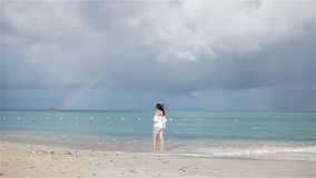 Young beautiful woman on tropical seashore with rainbow on background. Happy girl relaxing at white sand tropical beach stock video footage