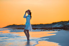 Young beautiful woman on tropical seashore in sunset. Happy girl in dress in the evening on the beach Royalty Free Stock Photo