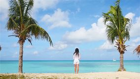 Young beautiful woman on tropical seashore. Happy girl relaxing at white sand tropical beach. Young beautiful woman on tropical seashore between two palms. SLOW stock video footage
