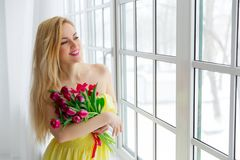 Young beautiful woman with tulip bunch in yellow dress looks at window. Stock Photography