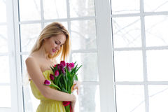 Young beautiful woman with tulip bunch in yellow dress. 8 march international womens day. Young beautiful woman with tulip bunch in yellow dress. 8 march Stock Image