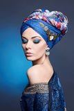 Young beautiful woman in turban. Portrait of young beautiful woman close up. Perfect makeup. Perfect skin. Fashion photo.Beauty lady with colored turban over Stock Photo