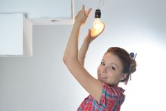 Young beautiful woman twists a bulb Royalty Free Stock Images