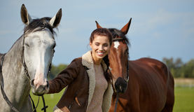 Young beautiful woman and two horses Royalty Free Stock Photos