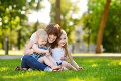 Young beautiful woman and two little kids hugging Royalty Free Stock Photos