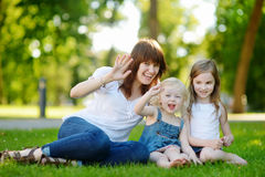 Young beautiful woman and two little kids hugging Stock Images
