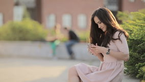 Young Beautiful Woman Is Typing A Message On The Phone Sitting On The Street. Young Beautiful Girl With Long Hair In The City At Sunset stock video