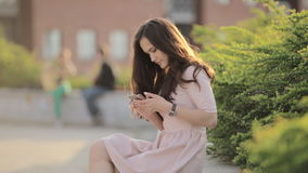 Young Beautiful Woman Is Typing A Message On The Phone Sitting On The Street. Young Beautiful Girl With Long Hair In The City At Sunset stock video footage