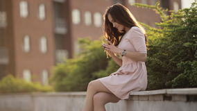 Young Beautiful Woman Is Typing A Message On The Phone Sitting On The Street. Young Beautiful Girl With Long Hair In The City At Sunset stock footage