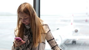 Young beautiful woman typing on mobile phone at the airport. Attractive girl is waiting a flight in airport waiting room. Girl is standing at the window behind stock video