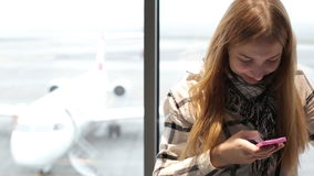 Young beautiful woman typing on mobile phone at the airport. Attractive girl is waiting a flight in airport waiting room. Girl is standing at the window behind stock video footage