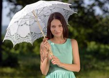 Young beautiful woman with umbrella in the park Stock Photo