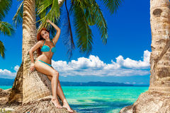 Young beautiful woman under the palm trees on a tropical island. Royalty Free Stock Photo