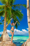 Young beautiful woman under the palm trees on a tropical island. Royalty Free Stock Images