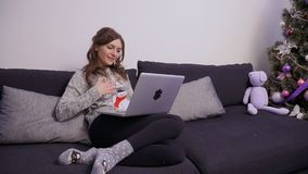 Young beautiful woman use laptop relaxing on sofa near Christmas tree stock video footage