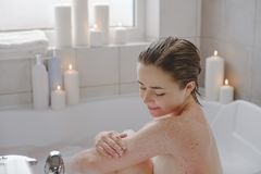 A young beautiful woman uses a body srab in a bath. stock photos