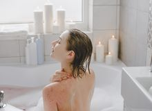 A young beautiful woman uses a body srab in a bath. royalty free stock photos