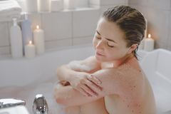 A young beautiful woman uses a body srab in a bath. stock images