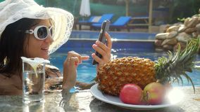 Young beautiful woman uses mobile phone in swimming pool and drinks water next to plate with tropical fruits. 3840x2160. Young beautiful woman uses mobile phone stock video