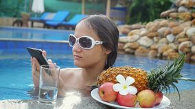 Young beautiful woman uses mobile phone in swimming pool next to the glass of the water and plate with tropical fruits. In slow motion. 1920x1080 stock video footage
