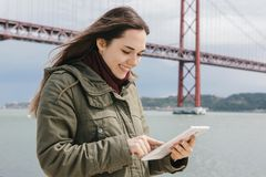 A young beautiful woman uses a tablet to communicate with friends or looks at a map or something else. Bridge April 25 Stock Photos