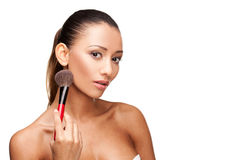 Young beautiful woman using brush to apply makeup Royalty Free Stock Images