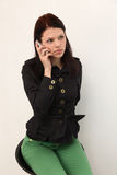 Young beautiful woman using cell phone. Young beautiful woman  sits on a chair using cell phone Royalty Free Stock Photo