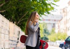 Young beautiful woman using cell phone while holding skateboard stock images
