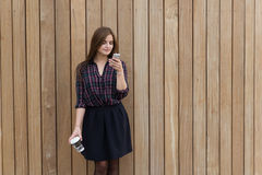 Young beautiful woman using cell telephone while standing with take away coffee against wooden wall with copy space Royalty Free Stock Images