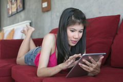 Young beautiful woman using computer tablet on red sofa Royalty Free Stock Images