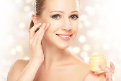 Young beautiful woman using a face cream Stock Photography