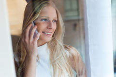 Young beautiful woman using her mobile phone at home. Royalty Free Stock Photography