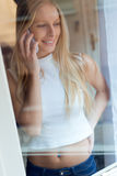 Young beautiful woman using her mobile phone at home. Stock Images